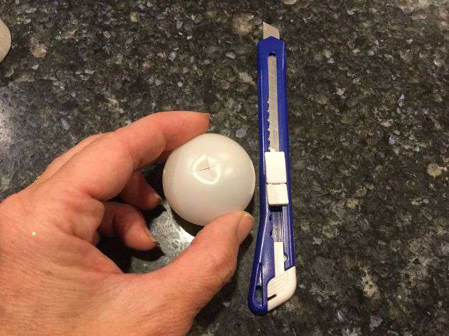 """Cut an """"X"""" in the bottom of the ping pong ball. This step is not for kids - I prepped this part for the class parties. You could try to have kids cut with something else like scissors, or a poke it with an ice pick."""