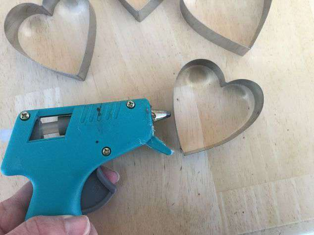 Put a little glue near the bottom of one of the cookie cutters.