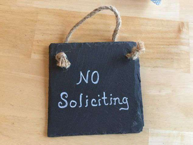 Using the paint marker, write no soliciting on your sign.