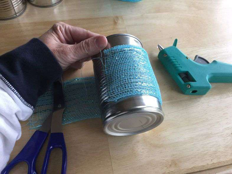 First cut your ribbon to fit your can. Place a line of hot glue and stick one side of your ribbon on it.