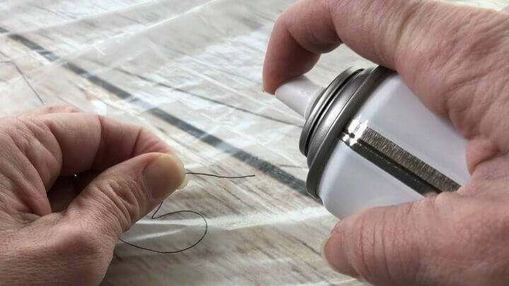 Spray a little hairspray on the end of the thread and let it dry.