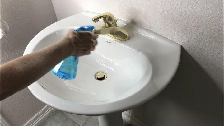 Spray rubbing alcohol onto your sinks and faucets. Wipe off with a paper towel. It'll not only clean disinfect your sinks and faucets, but it'll shine them right up too.