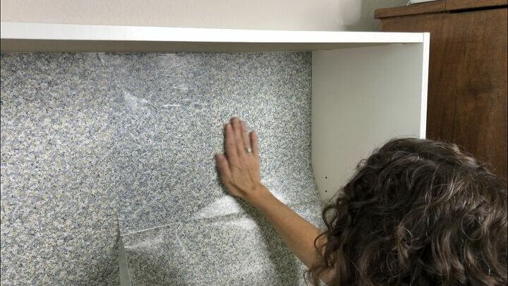 I added contact paper to the back panel of the bookshelf. Place the contact paper by an edge, slowly peel the backing off and slide your hand back and forth to prevent bubbles from forming. If you make a mistake, just peel it up and try again.