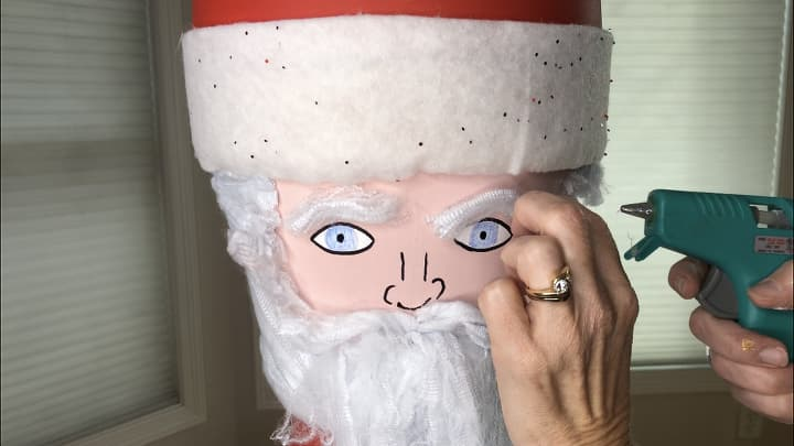 I hot glued on fake cobweb for hair, beard, mustache, and eye brows. I drew his eyes and nose on, as well as gave him rosy cheeks with a pink crayon.