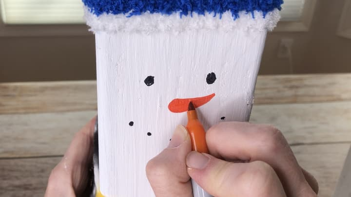 I drew a snowman face on each post with permanent markers. You could also use paint.
