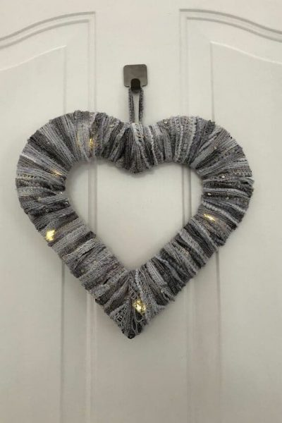 I found some beautiful yarn from a thrift store for $1. I then ran to Dollar Tree and picked up a heart wreath and a battery operated strand of LED lights. For $3, I made a heart wreath - great for Valentine's Day or keep it up all year.