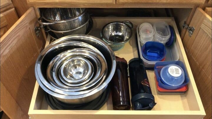 This is the top drawer in that same cabinet and I used a stacking system here as well. All of the lids that fit those stainless bowls are in order directly underneath them. My colanders/strainers are all stacked in the back. The few plastic containers (with the correct number and BPA Free) that I kept are all organized by stacking with appropriate lids in a large size plastic container to keep them together.