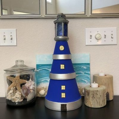 I just love the beach and I've been looking for creative ways to incorporate beachy decor into my home. This flower pot lighthouse is the perfect project to accent my shell collection! With just a few easy to find materials you can have your own nifty flower pot lighthouse in under an hour or two. This project is so easy that you don't need any crafting experience in order to do it yourself. Check out my step by step guide and get started!