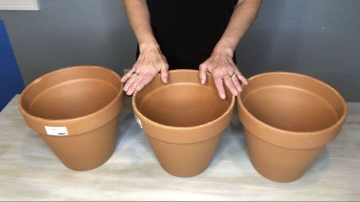 """set of 3 10"""" terra cotta flower pots on table with woman's hands"""