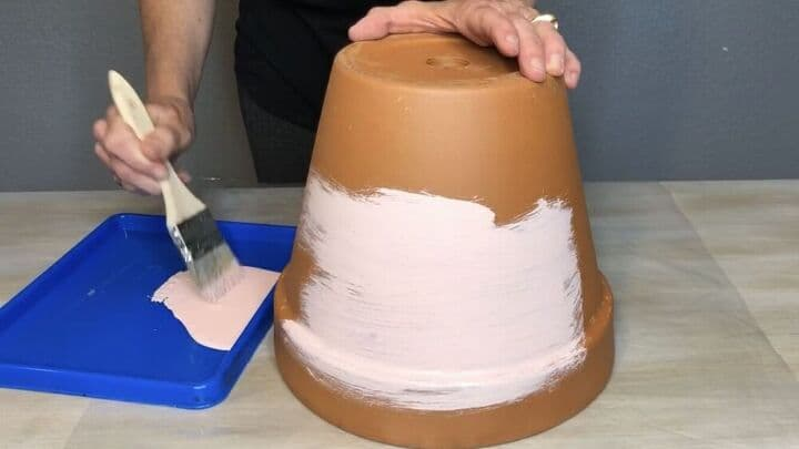Shown painting the terracotta pots with paint brush and blue paint tray