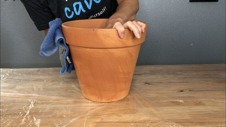"""I'm using 10"""" terra cotta flower pots. Make sure to remove the labels from the flower pots. Then wipe them down with a wet towel to remove any dirt or debris on them. This is important because if they are dirty the paint won't stick properly. Let them dry completely before you start painting."""