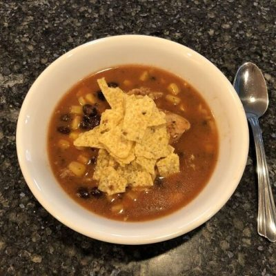 To serve, place soup in a bowl, top with shredded cheese and crushed tortilla chips.
